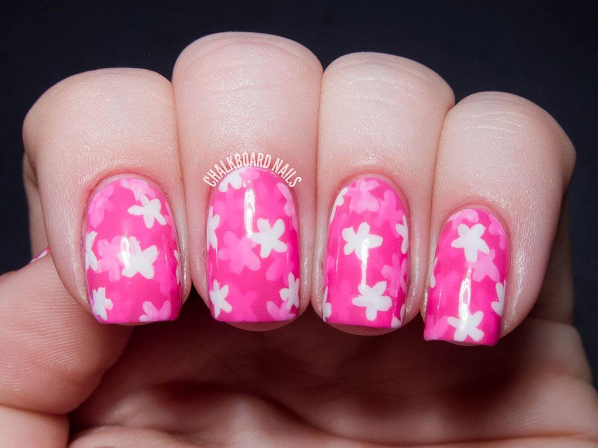 Ongles roses avec fleurs blanches