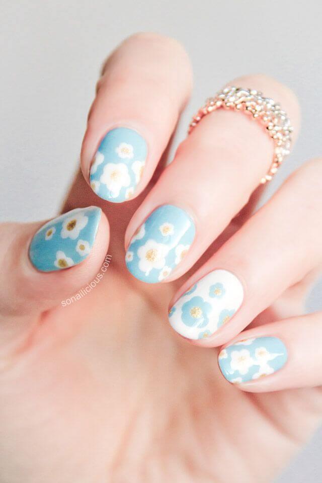 Ongles bleu clair avec des fleurs facilement dorées et blanches